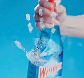 Cleaning smudges on glass with Windex